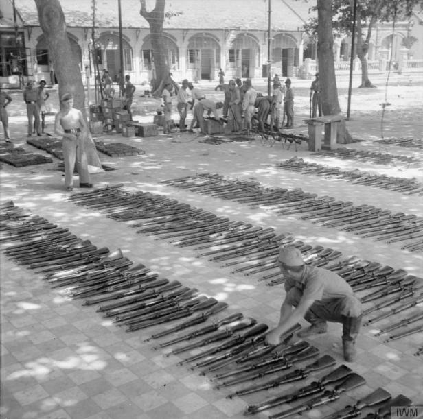 British-officers-watch-as-Japanese-prisoners-of-war-clean-and-oil-the-thousands-of-surrendered-Arisaka-rifles-at-the-prisoner-of-war-camp-at-Cape-Saint-Jacques (1)